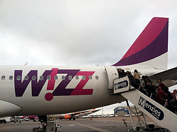 Sacred Harp singers board a bright pink Wizz Air plane. Photograph by Lauren Bock.